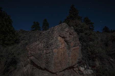 Pictographs on granite boulder at night, Naramata, British Columbia, Canada
