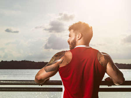 athletic wear: Rear view portrait of young muscular man taking a break from training on lake pier LANG_EVOIMAGES