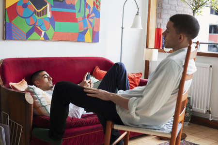 modern living room: Young men relaxing in living room LANG_EVOIMAGES
