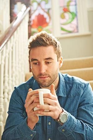 sit down: Hombre con taza en las escaleras LANG_EVOIMAGES
