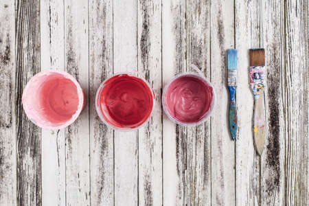 Still life of pink paint containers and blue paint brush
