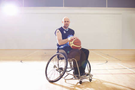Wheelchair basketball player holding ball LANG_EVOIMAGES