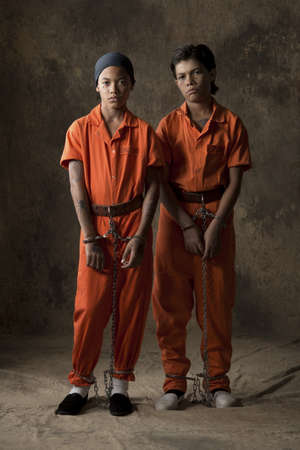 Studio portrait of two boys in handcuffs and chains