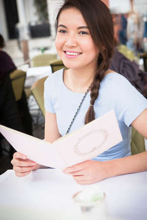 groovy: Young woman sitting at table at outdoor restaurant, holding menu