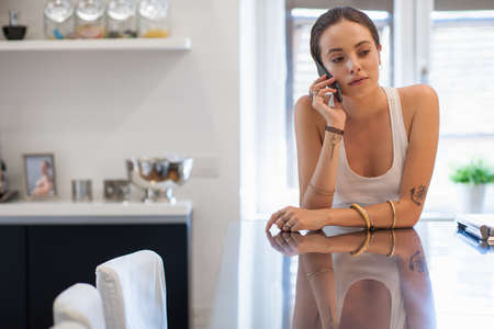 Sad looking young woman leaning on kitchen table chatting on smartphone LANG_EVOIMAGES