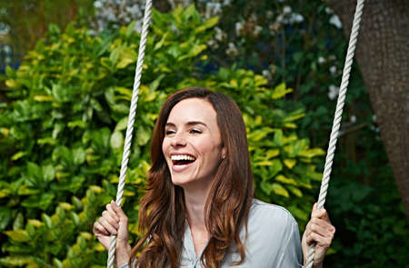 Woman laughing on swing