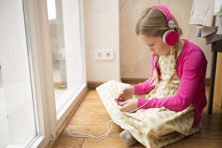 Girl sitting on floor selecting music for headphones