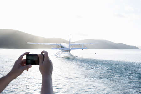 Womans hands photographing seaplane taking off from Long Island, Whitsunday Islands, Queensland, Australia