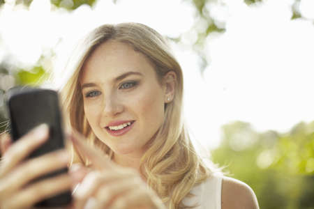 Young woman using smartphone touchscreen in park
