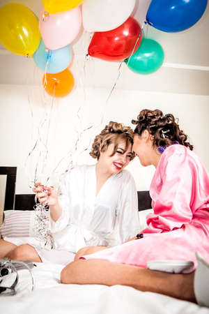 Two young female friends with balloons laughing on bed