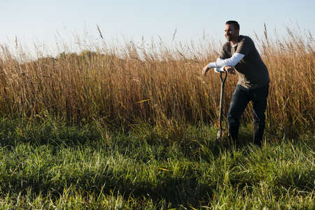 30 years old man: Portrait of mid adult male farmer leaning on spade in field, Plattsburg, Missouri, USA