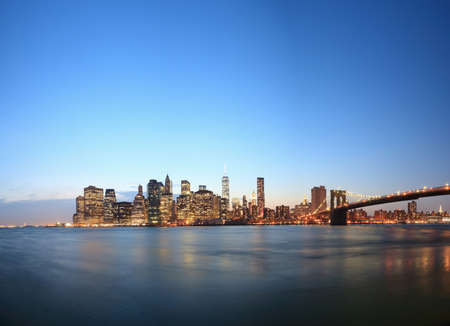 View of Lower Manhattan skyline and Brooklyn Bridge at dusk, New York, USA LANG_EVOIMAGES