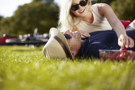 Young woman reaching for strawberries whilst boyfriend lying in park