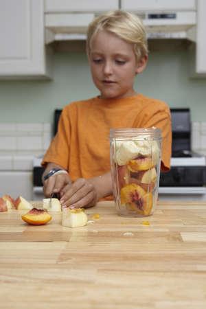 low self esteem: Boy blending fruits in kitchen