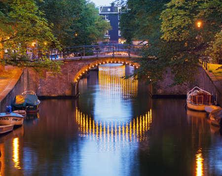 traditionally dutch: Canal bridge illuminated at dusk, Amsterdam, Netherlands