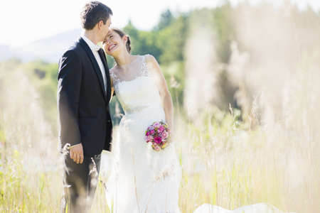 Candid portrait of bride and bridegroom in field LANG_EVOIMAGES