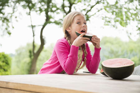 Girl at patio table eating watermelon slice