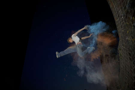 all under 18: Parkour athlete experimenting with movement and powder paint at Balcombe Viaducts, Sussex, United Kingdom