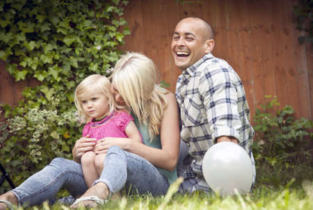 Happy couple sitting with toddler daughter in garden