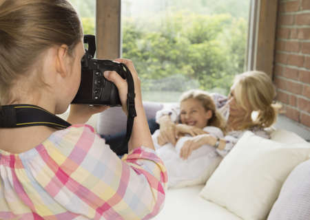 Daughter taking photograph of mother and sister