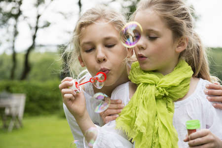 Two sisters blowing bubbles LANG_EVOIMAGES