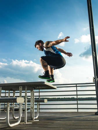 Young man jumping backwards from picnic table on lake pier