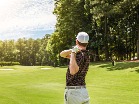 Rear waist up view of young male golfer teeing off on golf course, Apex, North Carolina, USA