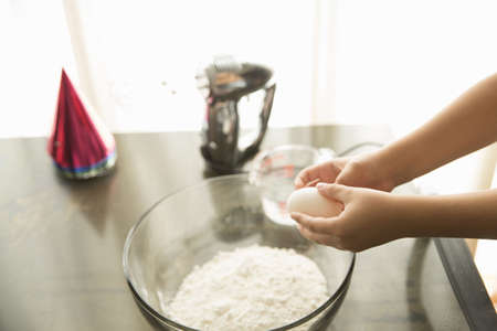 measuring cup: Hand holding egg over mixing bowl on table