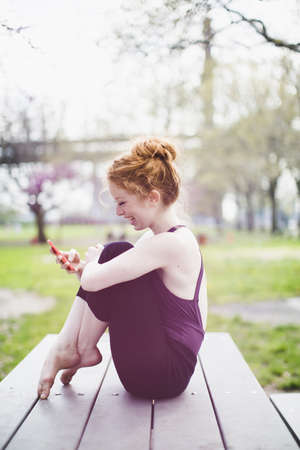 Modern dancer striking a pose and using a smart phone in a urban park LANG_EVOIMAGES