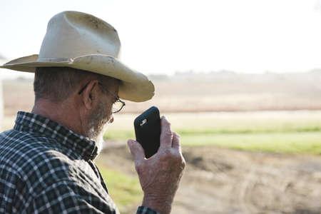 environmental issues: Over shoulder view of senior male farmer holding up smartphone, Plattsburg, Missouri, USA
