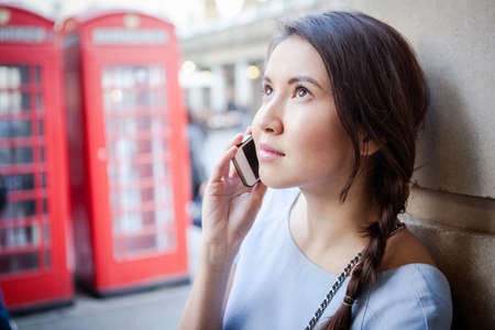 Young woman on smartphone, in front of red London telephone box