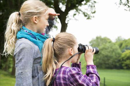 Two sisters using binoculars