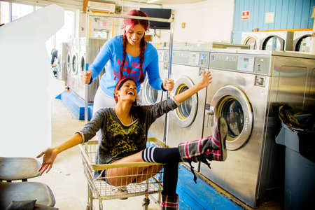 go inside: Two young women in laundromat, one pushing the other along in trolley