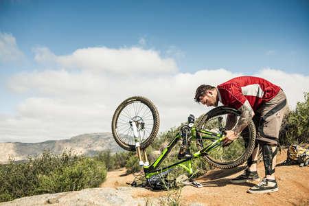 Downhill mountain biker fixing bike LANG_EVOIMAGES