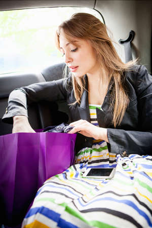 Young woman in back of taxi, looking in shopping bag