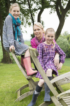 Mother and daughters sitting on wooden chair, portrait