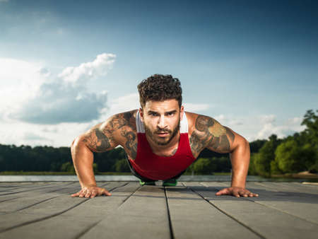 athletic wear: Surface level portrait of young man doing push ups on lake pier LANG_EVOIMAGES