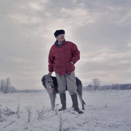 Portrait of man with deerhound in snow covered field
