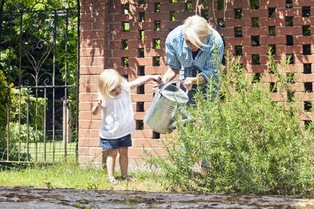 Female toddler helping mother with watering can in garden