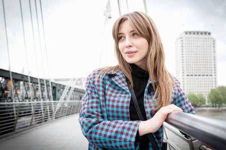 Portrait of young female tourist gazing from Golden Jubilee footbridge, London, UK