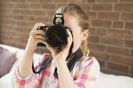 obscuring: Girl taking photograph towards camera