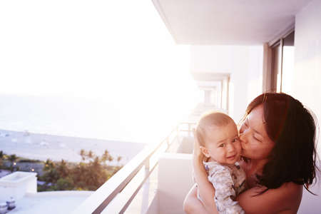 balcony: Portrait of mid adult mother and baby son on apartment balcony