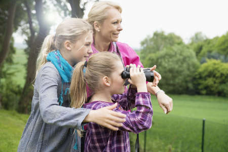 Mother and daughters using binoculars