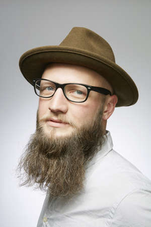 Studio portrait of mid adult man in trilby with overgrown beard