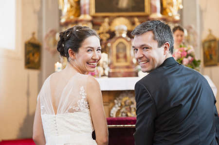 marrying: Rear view of bride and bridegroom at church altar
