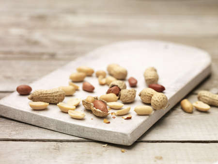 Peanuts, whole and cracked open monkey nuts on wooden chopping board LANG_EVOIMAGES