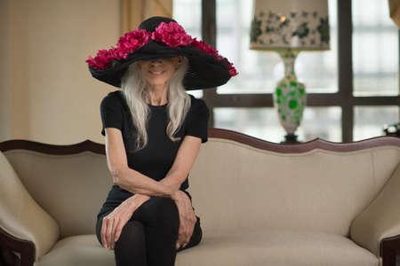Portrait of elegant senior woman with bonnet on sofa