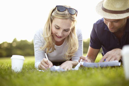 Couple lying in park writing on paper