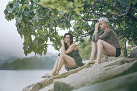 Two young women sitting  on harbor rocks