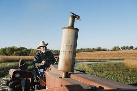 environmental issues: Senior male farmer driving tractor on rural road, Plattsburg, Missouri, USA LANG_EVOIMAGES